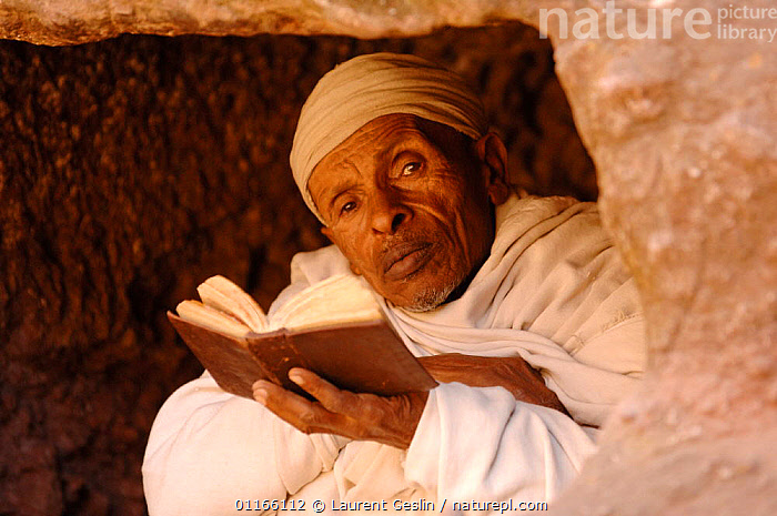 Christian worshipper near St Sauveur's church, Lalibela, North Ethiopia. These worshippers stay for hours in a hole in the carved rock to read their holy books. 2006  ,  BIBLE,EAST AFRICA,PEOPLE,READING,RELIGION,Africa,EAST-AFRICA  ,  Laurent Geslin