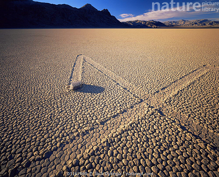 Boulder with zig-zag trails across a dry lake bed, sunset, Ubehebe Peak in distance, The Racetrack Playa, Death Valley National Park, California  ,  CALIFORNIA,CRYPTIC,DRY,LAKES,LANDSCAPES,MOUNTAINS,NORTH AMERICA,NORTH AMERICA,ROCKS,TRACKS,USA,WEIRD,Catalogue1  ,  Jack Dykinga