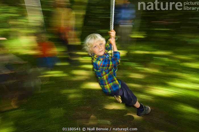 Young boy swinging through the forest, Letham, Fife, Scotland, UK, ABSTRACTS,CHILD,CHILDHOOD,CHILDREN,EUROPE,FOREST,FUN,JULY,MOVEMENT,OUTDOORS,PEOPLE,PLAYING, Niall Benvie