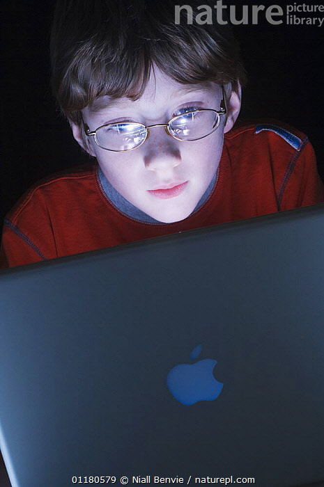 Boy, 9, engrossed by a computer, December, Scotland, UK - model released, BEHAVIOUR,CHILD,CHILDREN,COMPUTERS,EUROPE,PEOPLE,PRIMATES,SCOTLAND,VERTEBRATES,VERTICAL,Mammals, Niall Benvie