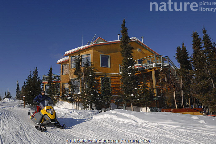 Blachford Lake Lodge, an environmentally friendly and remote fly-in lodge, and man on skidoo, Northwest Territories, Canada. March 2007  ,  HOTELS,LODGES,NORTH AMERICA,PEOPLE,SNOW,TOURISM,WINTER,CANADA  ,  Eric Baccega