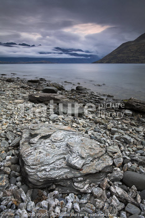 Rocky shores of Lake Wakatipu, near Queenstown, South Island, New Zealand  ,  AUSTRALASIA,CLOUDS,LAKES,LANDSCAPES,MOUNTAINS,NEW ZEALAND,ROCKS,VERTICAL,Weather  ,  Adam Burton