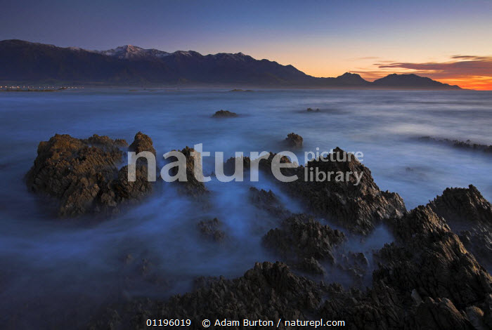Dawn over the Southern Ocean, looking towards the town of Kaikoura, South Island, New Zealand  ,  AUSTRALASIA,COASTS,DAWN,LANDSCAPES,MOUNTAINS,NEW ZEALAND,ROCKS,SUNRISE  ,  Adam Burton