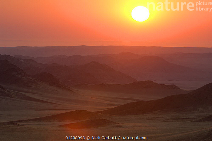 Rolling hills and mountains at sunrise. Skeleton Coast Park, Namibia. July 2008.  ,  LANDSCAPES,SOUTHERN AFRICA,SUN  ,  Nick Garbutt