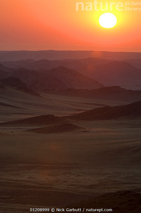 Rolling hills and mountains at sunrise. Skeleton Coast Park, Namibia. July 2008.  ,  DAWN,LANDSCAPES,SOUTHERN AFRICA,SUN,VERTICAL  ,  Nick Garbutt