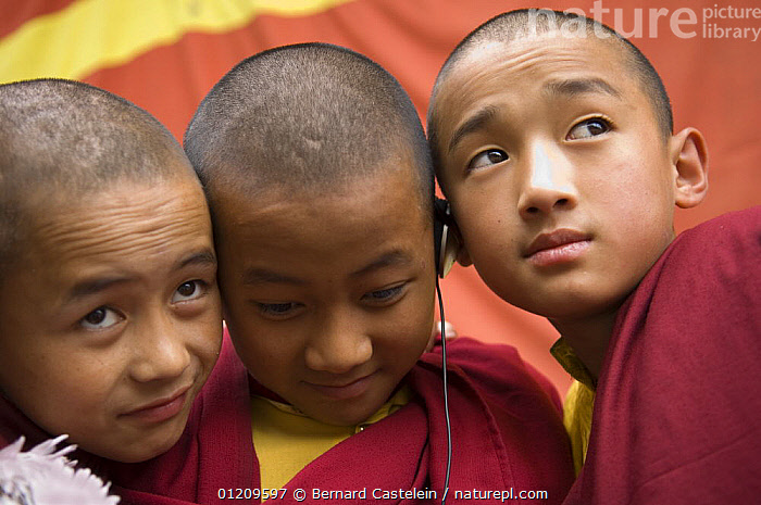 Young buddhist monks listening to a sound recording of monk chanting on an ipod, Enchey Monastery, Gangtok, Sikkim, India October 2007  ,  ASIA,BOYS,BUDDHISM,BUDDHIST,CHILDREN,FACES,GROUPS,INDIA,MODERN,MONK,MUSIC,PEOPLE,TECHNOLOGY,THREE  ,  Bernard Castelein