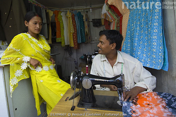 Tailor and woman with sewing machine in street market of Sombare, West Sikkim, India October 2007  ,  ASIA,CLOTHES,INDIA,MEN,PEOPLE,SEWING,TRADITIONAL,WOMEN  ,  Bernard Castelein