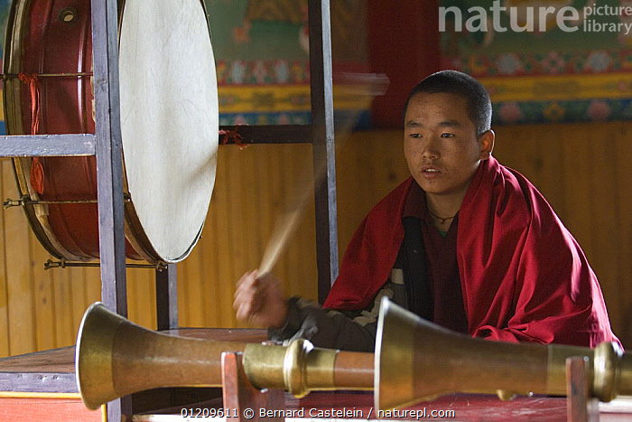 Young Buddhist monk during puja, Anden Gumpa, between Sombare and Hilley, West Sikkim, India October 2007  ,  ASIA,BUDDHISM,BUDDHIST,INDIA,INDOORS,INSTRUMENTS,MEN,PEOPLE,TRADITIONAL  ,  Bernard Castelein