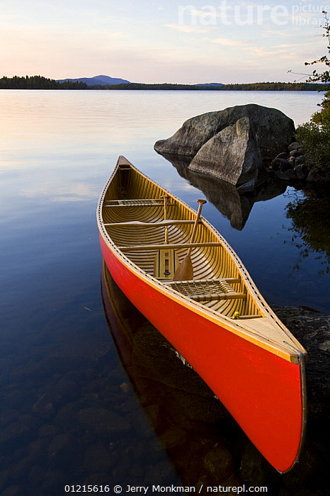 An empty canoe on the shoreline of Seboies Lake near Millincoket, Maine, USA.  ,  ARTY,BOATS,CANOEING,LAKES,LANDSCAPES,LEISURE,NEW ENGLAND,RED,USA,VERTICAL,WATER,North America,SPORTS, WATERSPORTS, WATERSPORTS, WATERSPORTS  ,  Jerry Monkman