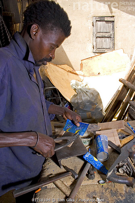 Craftsman cutting up discarded drinks cans, Dakar, Senegal, 2008, AFRICA,ARTIFACTS,CANS,CRAFTS,INDUSTRY,MALES,METALS,PEOPLE,RECYCLING,VERTICAL,WEST AFRICA,WEST-AFRICA, Tom Gilks