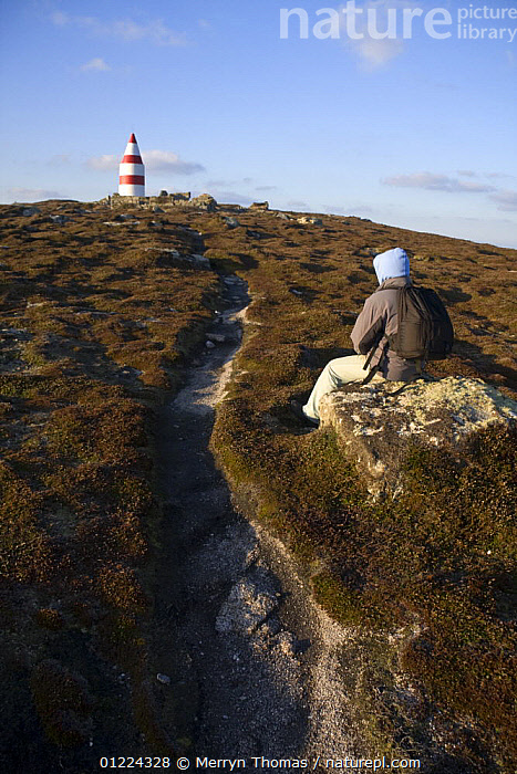 Walker sitting near the Daymark, erected in the 1600s. St.Martin's, Isles of Scilly December 2008.  ,  COASTS,CORNWALL,DAYMARKS ,ENGLAND,EUROPE,FOOTPATHS,HEATHER,HIKING,LANDSCAPES,MARKERS,MOORLAND,PEOPLE,SAINT MARTINS,STRIPES,UK,WINTER,NAVIGATION, United Kingdom, United Kingdom, United Kingdom  ,  Merryn Thomas