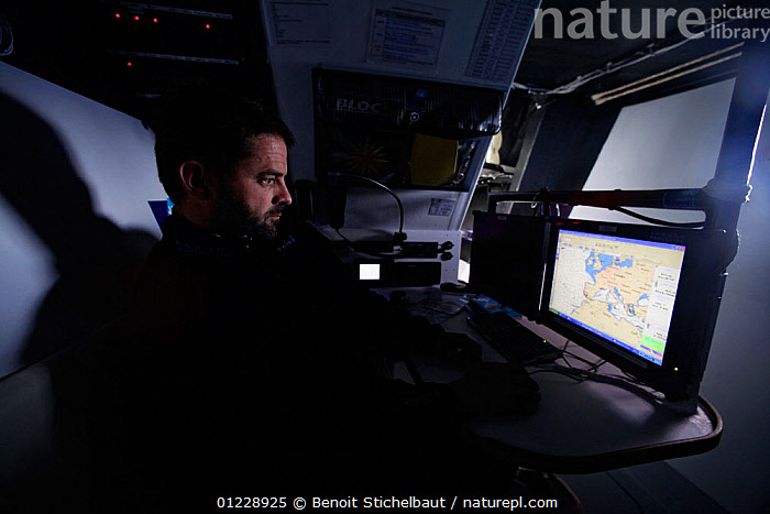 """Skipper Pascal Bidegorry in the navigation room aboard Maxi yacht """"Banque Populaire V"""", practicing off Cadiz, Spain. March 2009.  ,  CONPUTERS ,EUROPE,INSTRUMENTS,INTERIORS,MAN,NAVIGATING,NAVIGATION,NIGHT,PRACTICING,SAILING BOATS,SITTING,SKIPPER,SPAIN,TRIMARANS,YACHTS,BOATS ,CREWS ,PEOPLE  ,  Benoit Stichelbaut"""