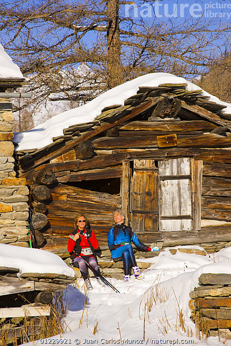 Cross country skiers resting outside wooden cabin in Gran Paradiso NP, Valnontey, Aosta valley, Italian alps., ALPS,BUILDINGS,EUROPE,HIKING,ITALY,LANDSCAPES,LEISURE,MOUNTAINS,NP,PEOPLE,RESERVE,SNOW,SUNNING,VALLE,VALNONTEY,VERTICAL,National Park, Juan Carlos Munoz