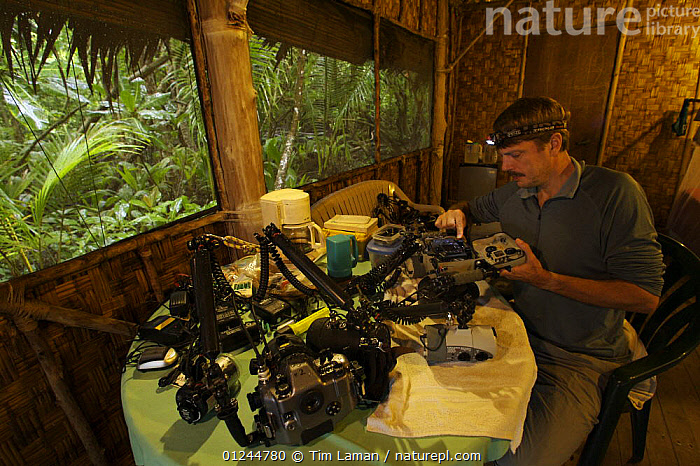 Photographer Tim Laman prepares underwater camera at the Kosrae Village Ecolodge, a rainforest lodge on Kosrae Island, Federated States of Micronesia. Model released, June 2005, BUILDINGS,CAMERAS,EQUIPMENT,INDOORS,MICRONESIA,OCEANIA,PACIFIC ISLANDS,PEOPLE,PHOTOGRAPHY,TROPICAL RAINFOREST, Tim Laman