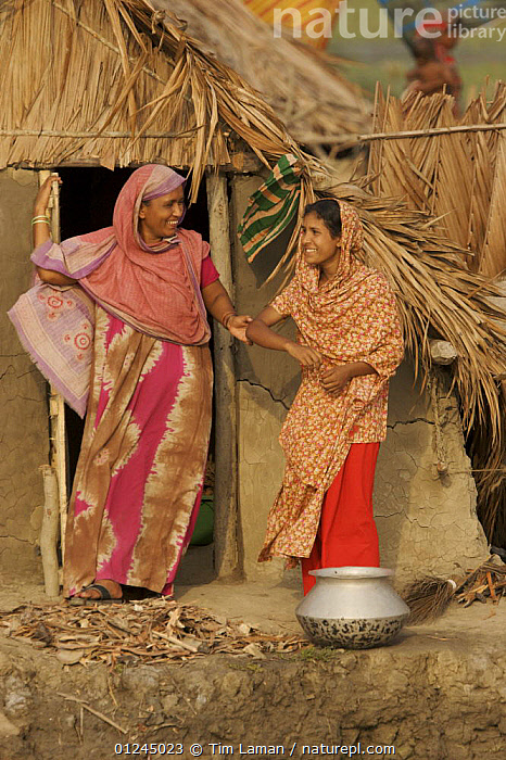 Two women in the village of Chandpai on the Passur River, where shrimp fry fishing to supply shrimp for the shrimp ponds is the main industry. Villagers live in simple mud and thatch huts that are washed away by high waters every year. Sunderbans, Khulna Province, Bangladesh, April 2006, ASIA,BANGLADESH,BUILDINGS,COASTS,COMMERCIAL,CRUSTACEANS,INVERTEBRATES,LANDSCAPES,MANGROVE,MANGROVES,MARINE,PEOPLE,RIVERS,SHRIMP FARMING,SHRIMPS,SUNDARBAN,SUNDARBANS,SUNDERBANS,VERTICAL,VILLAGES,INDIAN-SUBCONTINENT, Tim Laman