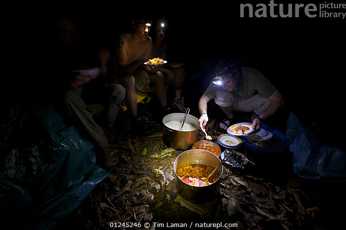 Expedition members serve themselves dinner of rice and red sauce with sardines and spam, Bioko Island, Equatorial Guinea, Rapid Assessment Visual Expedition, International League of Conservation Photographers, January 2008. Model released, CAMPING,CENTRAL AFRICA,FEEDING,FOOD,ILCP,NIGHT,PEOPLE,RAVE,TROPICAL RAINFOREST,Africa, Tim Laman