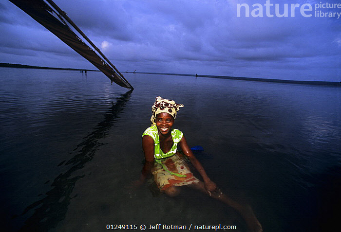 Fisherwoman relaxes in water after night of fishing, Inhassoro, Mozambique, November 2008  ,  BOATS,COASTS,DAWN,FISHING,PEOPLE,SOUTHERN AFRICA,SUNRISE  ,  Jeff Rotman