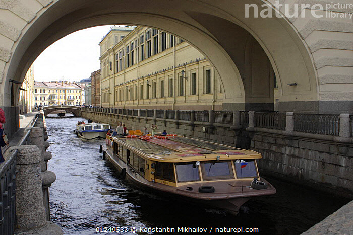 Tourist boat passing under a bridge on one of the many channels of the River Nega in St Petersburg, Russia, June 2007  ,  BOATS,BRIDGES,BUILDINGS,CITIES,EUROPE,LANDSCAPES,PASSENGER FERRIES,PEOPLE,RIVERS,RUSSIA,TOURISM, WORKING-BOATS ,CIS, WORKING-BOATS  ,  Konstantin Mikhailov