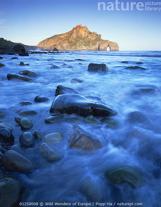 Sea over smooth rocks with rock arch in distance, Gaztelugatxe coast, Basque country, Bay of Biscay, Spain, October 2008  ,  ARCHES,BLUE,BUILDINGS,COASTS,EUROPE,LANDSCAPES,ROCK FORMATIONS,ROCKS,SEA,SPAIN,VERENA POPP HACKNER,VERTICAL,WWE,Geology  ,  Wild Wonders of Europe / Popp-Ha