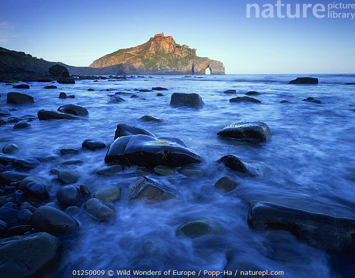 Sea over smooth rocks with rock arch in distance, Gaztelugatxe coast, Basque country, Bay of Biscay, Spain, October 2008  ,  ARCHES,ATLANTIC,BAY OF BISCAY,BLUE,COASTS,EROSION,EUROPE,LANDSCAPES,ROCK FORMATIONS,ROCKS,SEA,SPAIN,VERENA POPP HACKNER,WWE,Geology,Marine  ,  Wild Wonders of Europe / Popp-Ha