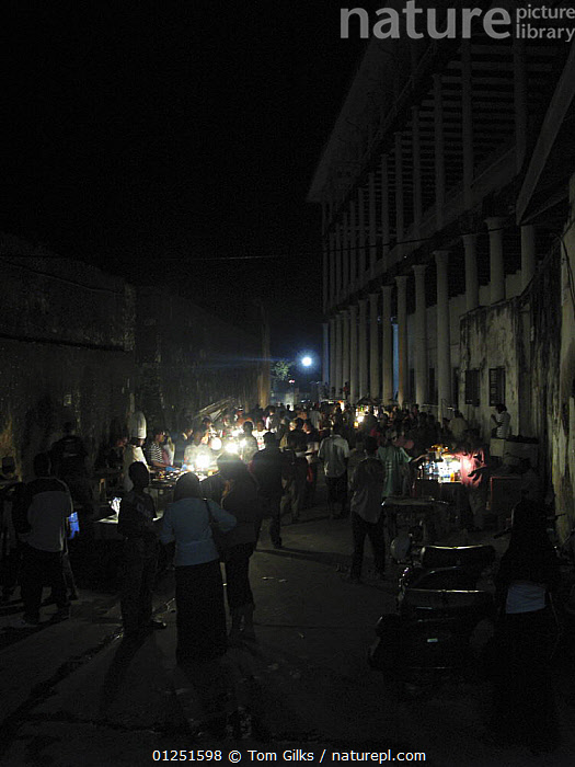 Food stalls at night, next to The House of Wonders, Stone Town, Zanzibar, Tanzania. August 2008.  ,  AFRICA,BUILDINGS,EAST AFRICA,MARKETS,NIGHT,PEOPLE,TRADE,VERTICAL  ,  Tom Gilks