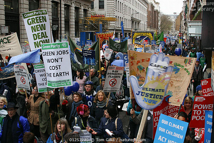 """Protesters carrying signs / banners """"Green jobs won't cost the earth"""" and  """"Climate Justice now"""", part of 'The Wave' climate change march ahead of the Copenhagen climate summit, London, UK, 5th December 2009  ,  campaign,campaigning,CITIES,climate change,environment,ENVIRONMENTAL,EUROPE,GROUPS,PEOPLE,protesting,PROTESTS,SIGNS,UK,ENGLAND, United Kingdom, United Kingdom  ,  Tom Gilks"""