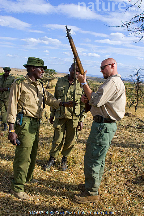 Security consultant (Ridgeback, Inc.) assisting in rifle cleaning and safety checks for Mara Conservancy rangers, Masai Mara Conservancy, Kenya, October 2006  ,  CONSERVATION,EAST AFRICA,GUARDS,GUNS,PEOPLE,POACHERS,POACHING,RANGERS,RESERVE,TRAINING,VERTICAL,WARDENS  ,  Suzi Eszterhas