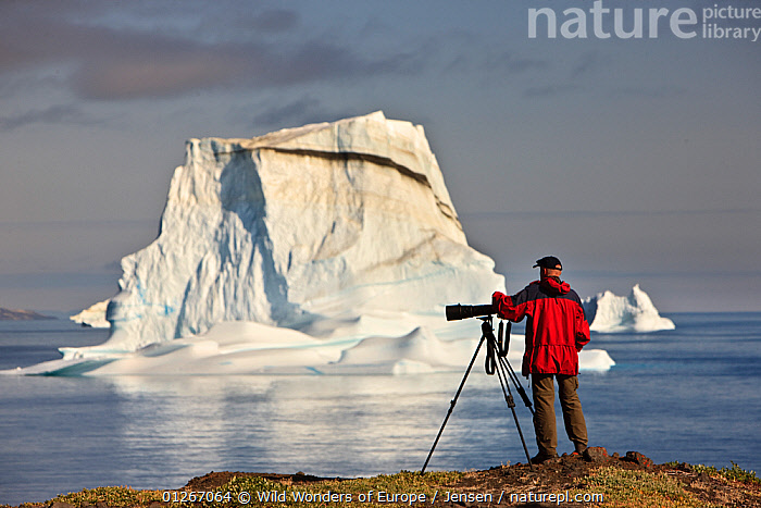 Photographer, Kai Jensen, on the coast near an iceberg, Qeqertarsuaq, Disko Bay, Greenland, August 2009  ,  ARCTIC,CAMERAS,COASTS,DISCOBAY,EUROPE,GREENLAND,ICEBERGS,KAI JENSEN,LANDSCAPES,PEOPLE,REFLECTIONS,WWE  ,  Wild Wonders of Europe / Jensen