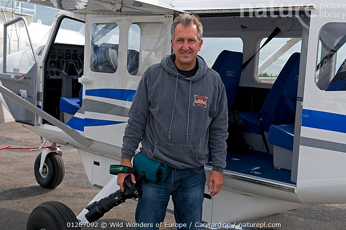 Photographer, Mark Carwardine, standing in front of plane used for aerial photography for Wild Wonders of Europe mission, Akureyri, Iceland, June 2009  ,  AEROPLANES,CAMERAS,EUROPE,ICELAND,MARK CARWARDINE,PEOPLE,WWE  ,  Wild Wonders of Europe / Carwardine