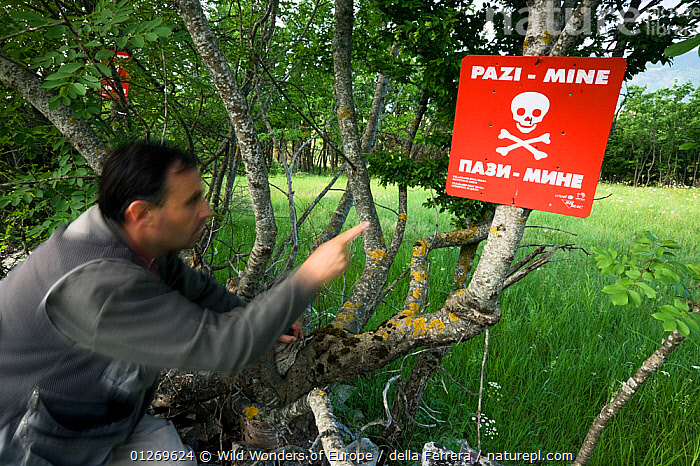 Person pointing at mine warning sign in a mine field near the village of Zadrzani, Northern Livanjsko Polje, an area affected by war (1991-1995) Bosnia and Herzegovina, May 2009  ,  BOSNIA AND HERZEGOVINA,DANGEROUS,EASTERN EUROPE,ELIO DELLA FERRERA,EUROPE,LANDSCAPES,PEOPLE,SIGNS,TREES,WWE,PLANTS  ,  Wild Wonders of Europe / della Ferrera