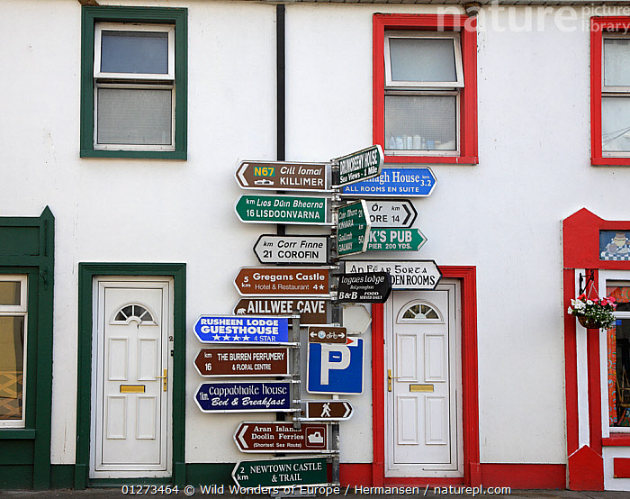 Sign post with a lot of signs in front of houses, Ballyvaughan, The Burren, County Clare, Ireland, June 2009  ,  BUILDINGS,EIRE,EUROPE,HOUSES,IRELAND,P�L HERMANSEN,SIGNS,TOURISM,VILLAGES,WWE  ,  Wild Wonders of Europe / Hermansen