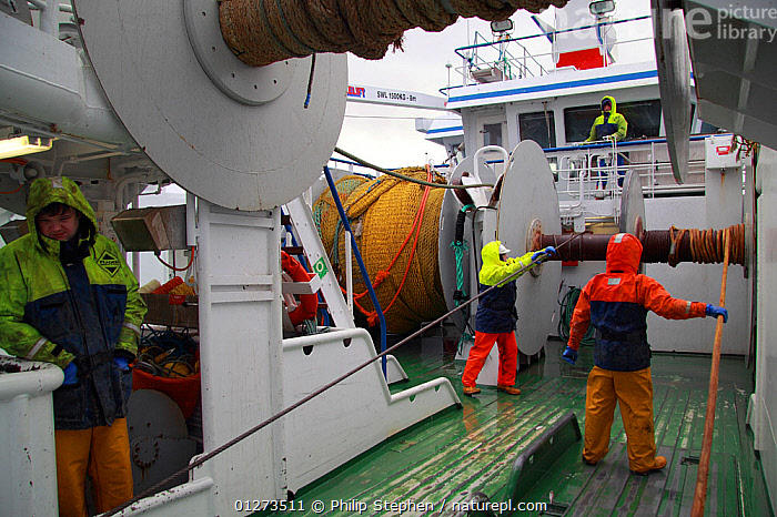 Fishermen guiding wires onto the netdrum while hauling the gear onboard a trawler, North Sea, January 2010.  ,  ABOARD,CREWS,EUROPE,FISHING BOATS,PROCEDURES,ROPES,TRAWLERS,WET WEATHER GEAR,BOAT-PARTS,BOATS, WORKING-BOATS  ,  Philip Stephen