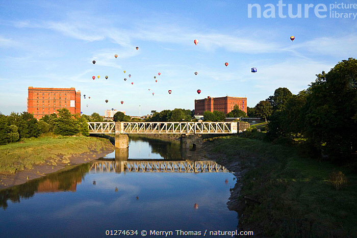 Bristol Balloon Fiesta over bridge and warehouses on the Avon River, Bristol, UK, August 2009.  ,  BALLOONS,BUILDINGS,CALM,CITIES,EUROPE,FESTIVAL,LANDSCAPES,REFLECTIONS,RIVERS,UK, United Kingdom  ,  Merryn Thomas