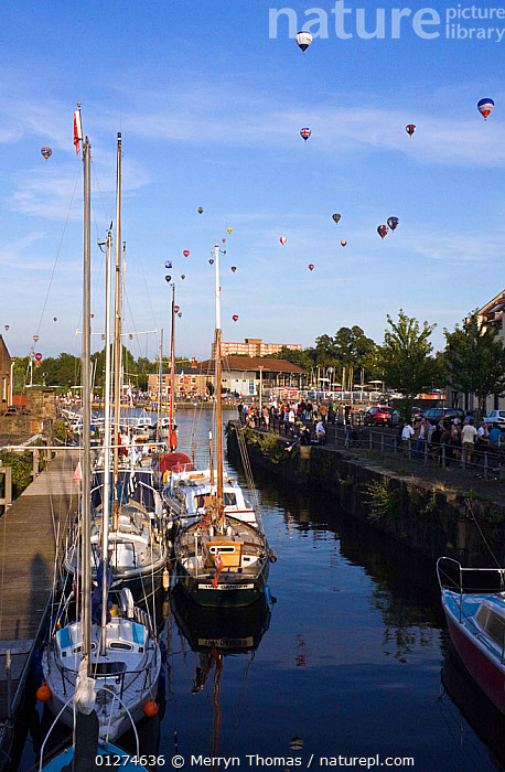 Bristol Balloon Fiesta over yachts moored on the Floating Harbour, Bristol, UK, August 2009.  ,  BALLOONS,CALM,CITIES,EUROPE,EVENTS,FESTIVAL,HARBOURS,LANDSCAPES,MARINAS,MOORED,RIVERS,SAILING BOATS,UK,VERTICAL,YACHTS, United Kingdom,BOATS  ,  Merryn Thomas