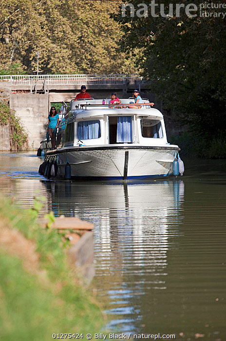 Family cruising on the Canal Du Midi near Carcassonne, Languedoc, France. July 2009. Model and property released.  ,  BRIDGES,CANALS,CRUISING,EUROPE,FAMILIES,FRANCE,FRONT VIEWS,MOTORBOATS,VERTICAL,BOATS  ,  Billy Black