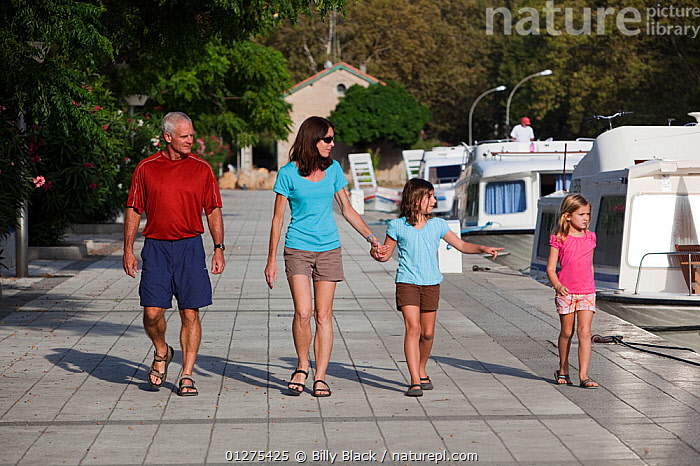 Family walking alongside boats, Canal Du Midi near Carcassonne, Languedoc, France. July 2009. Model and property released.  ,  CANALS,CRUISING,EUROPE,FAMILIES,FRANCE,HOLIDAYS,LEISURE,MOTORBOATS,BOATS  ,core collection xtwox  ,  Billy Black