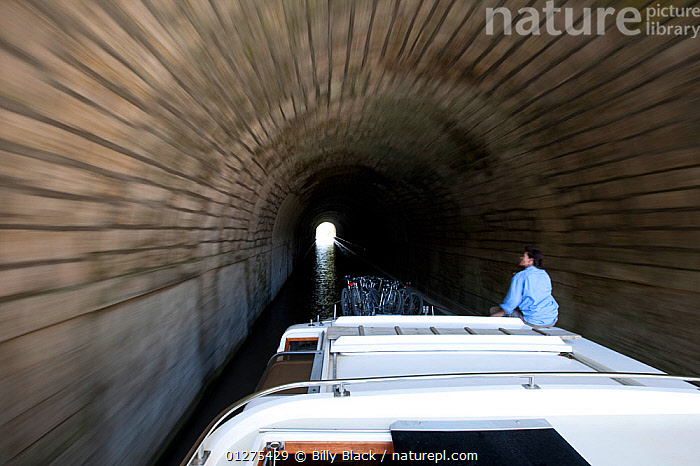 Woman on boat passing through a tunnel on the Canal Du Midi near Capestang, Languedoc, France. July 2009. Model and property released.  ,  ABOARD,ARTY SHOTS,CANALS,CRUISING,EUROPE,FRANCE,MOTORBOATS,MOVEMENT,PEOPLE,TUNNELS,BOATS  ,core collection xtwox  ,  Billy Black