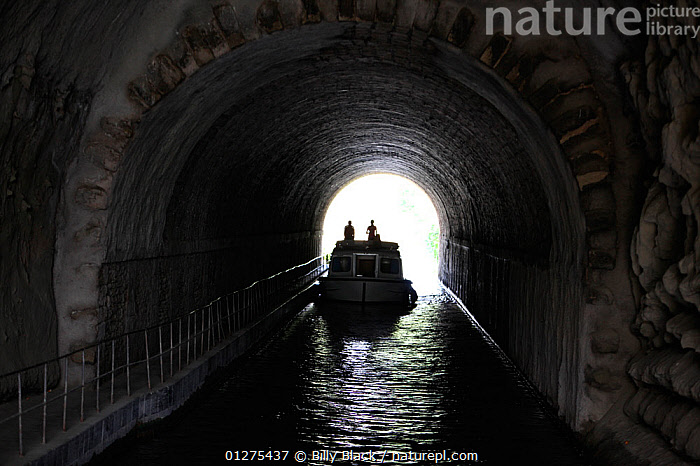 Boat passing through a tunnel on the Canal Du Midi near Capestang, Languedoc, France. July 2009. Model and property released.  ,  CANALS,CRUISING,DARK,EUROPE,FRANCE,MOTORBOATS,SILHOUETTES,TUNNELS,BOATS  ,core collection xtwox  ,  Billy Black