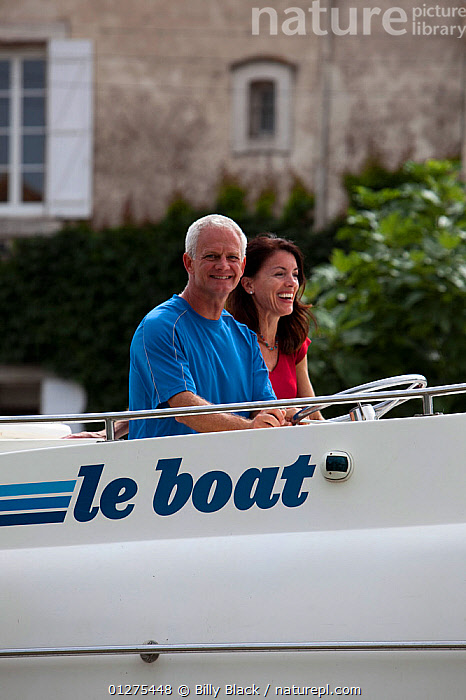Family cruising on the Canal Du Midi, Le Somail, France. July 2009. Model and property released.  ,  CANALS,CHARTER,COUPLES,CRUISING,EUROPE,FRANCE,HELMING,HOLIDAYS,LE BOAT,LEISURE,LIFESTYLE,MIDDLE AGED,MOTORBOATS,SMILING,VERTICAL,BOATS  ,PROCEDURES,CONCEPTS ,core collection xtwox  ,  Billy Black