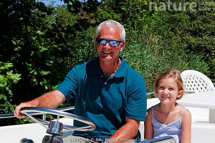 Man and girl cruising on the Canal Du Midi near Port de Bram, southern France. July 2009. Model and property released.  ,  ABOARD,CANALS,CRUISING,EUROPE,FRANCE,HELMING,HOLIDAYS,LEISURE,MOTORBOATS,OFFSPRING,PORTRAITS,SMILING,SUNGLASSES,BOATS  ,PROCEDURES,core collection xtwox  ,  Billy Black
