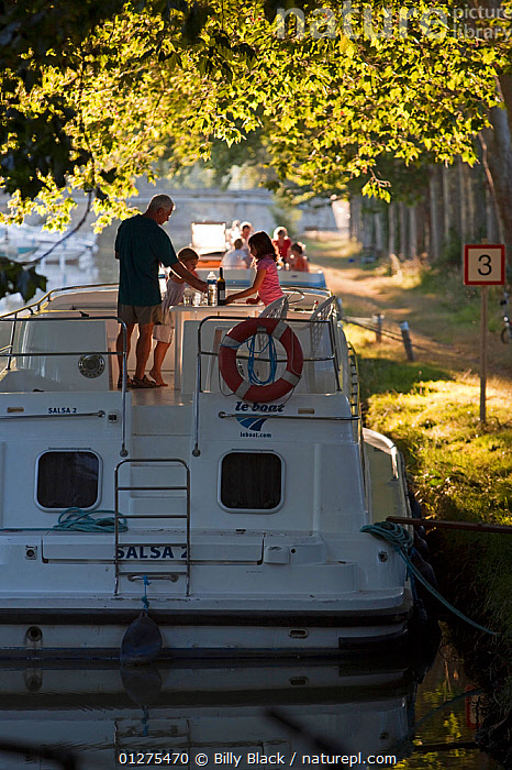 Family cruising on the Canal Du Midi near Port de Bram, southern France. July 2009. Model and property released.  ,  CANALS,CRUISING,DINNER,EUROPE,EVENING,FRANCE,HOLIDAYS,LEISURE,LIFESTYLE,MOORED,MOTORBOATS,PEACEFUL,REAR VIEWS,RELAXATION,SUMMER,VERTICAL,BOATS  ,Concepts,core collection xtwox  ,  Billy Black