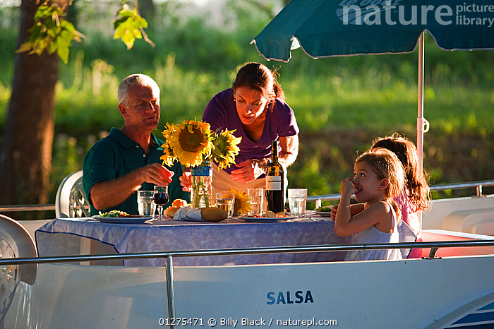 Family having dinner on the Canal Du Midi near Port de Bram, southern France. July 2009. Model and property released.  ,  CANALS,CRUISING,DINNER,EUROPE,EVENING,FAMILIES,FRANCE,HOLIDAYS,LEISURE,LIFESTYLE,MOTORBOATS,PEACEFUL,RELAXATION,SUMMER,BOATS  ,Concepts  ,  Billy Black