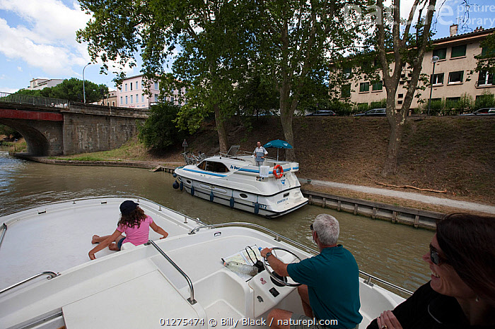 Family cruising on the Canal Du Midi, Carcassonne, southern France. July 2009. Model and property released.  ,  ABOARD,CANALS,CRUISING,EUROPE,FAMILIES,FRANCE,LEISURE,MOTORBOATS,PASSING,TOWNS,BOATS  ,  Billy Black