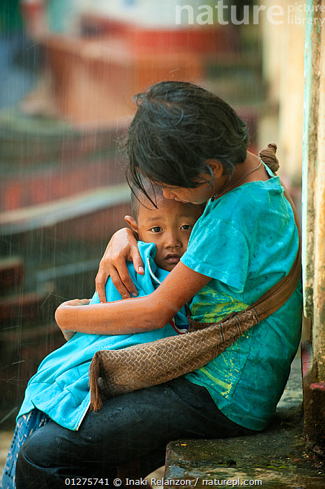 Two children, one sheltering the other, in heavy rain, during the monsoon, Bago, Myanmar, before Burma.  August 2009  ,  AFFECTIONATE,ASIA,BURMA,CHILDREN,CUTE,FAMILIES,PEOPLE,PORTRAITS,RAIN,RAINING,SOUTH EAST ASIA,VERTICAL,concepts,Weather  ,  Inaki Relanzon