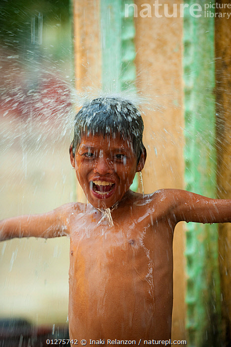 Boy playing in heavy monsoon rain, during the raining season, Bago, Myanmar, Burma.  August 2009  ,  ASIA,BURMA,CHILDREN,CUTE,ENJOYING,PEOPLE,PLAYING,PORTRAITS,RAIN,RAINING,SMILING,SOUTH EAST ASIA,VERTICAL,WATER,WEATHER,WET SEASON  ,  Inaki Relanzon
