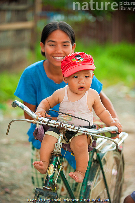 Portrait  of a little boy sat on the handlebars of a bicycle, in Inle Lake area, Shan State, Myanmar, Burma  August 2009  ,  ASIA,BABIES,BICYCLES,BURMA,CHILDREN,CUTE,PEOPLE,PORTRAITS,SMILING,SOUTH EAST ASIA,VERTICAL  ,  Inaki Relanzon