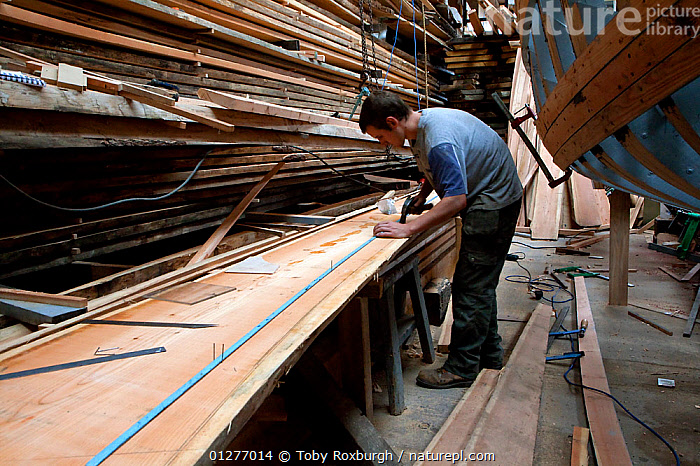 Man sketching the outline of hull planks during construction of a wooden fishing boat at the Underfall Yard, Bristol, England, UK, 2009. Model released.  ,  BOATS,BOATYARD,BOAT YARD,BOATYARDS ,BOAT YARDS,CONSTRUCTION,CUTTERS,DRY LAND,ENGLAND,EUROPE,FISHING BOATS,MAN,PEOPLE,PROCEDURES,UK,WOODEN,WORKING, SAILING-BOATS , United Kingdom  ,  Toby Roxburgh