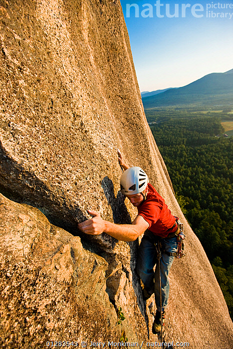 A man rock climbing near the top of Cathedral Ledge. Echo Lake State Park, White Mountains, in North Conway, New Hampshire, USA. October 2009, Model released, abseiling,ACTION,Active,activity,ADVENTURE,AUTUMN,Balance,CATALOGUE2,Cathedral Ledge,Caucasian,cliff face,CLIFFS,climber,CLIMBING,CONCENTRATION,crash helmet,Crevice,Echo Lake State Park,elevated view,HABITAT,Helmet,LEISURE,leisure activity,MALES,MAN,MOUNTAINS,new hampshire,new england,North Conway,NORTH AMERICA,one person,outdoors,PEOPLE,RECREATIONAL,rock climbing,rock face,ROCKS,ROPES,safety harness,skill,steep,USA,WATER,White Mountains,young adult,Geology,Model released,,Skill, Efficiency,, Jerry Monkman