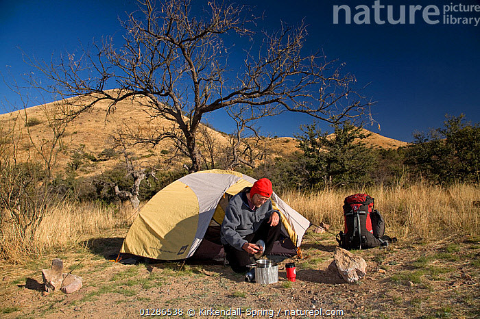 Hiker cooking beside his tent, at winter campsite in the Tumacacori Mountains of the Coronado National Forest. Arizona, USA, March 2009, model released  ,  CAMPING,COOKING,DESERTS,HIKING,LANDSCAPES,LEISURE,MALES,MAN,MOUNTAINS,NORTH AMERICA,PEOPLE  ,  Kirkendall-Spring