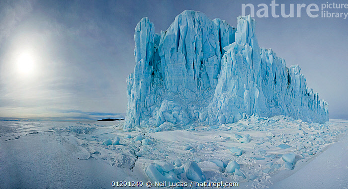 Glacier rising up out of sea ice with ice crack visible, Ross Sea, Antarctica, November 2008, ANTARCTICA,BLUE,CATALOGUE2,COLD,Crack,Frozen,GLACIERS,ICE,LANDSCAPES,lens flare,nature,Nobody,outdoors,POLAR,ROSS SEA,Scenics,sea,sea ice,SNOW,SUN,WHITE,Geology, Neil Lucas